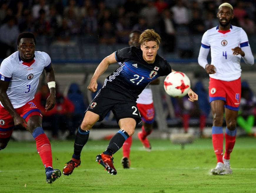 Japan's Gotoku Sakai (C) shoots the ball as Haiti's Mechack Jerome (left) and Jems Geffrard look on in an international friendly at Nissan Stadium on Tuesday night. The match ended in a 3-3 draw. | AFP-JIJI