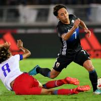 Japan's Shu Kurata (right) avoids a tackle from Haiti's Zachary Herivaux during their 3-3 draw at Nissan Stadium on Tuesday. | AFP-JIJI