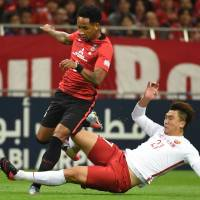 Urawa's Rafael Silva (left) and Shanghai's Shi Ke compete for the ball during the second leg of their Asian Champions League semifinal on Wednesday in Saitama. Reds won 1-0. | AFP-JIJI