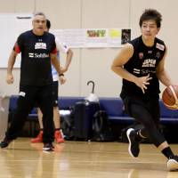Shooting guard Naoto Tsuji moves the ball as Japan head coach Julio Lamas watches during Wednesday's practice for the provisional Japan men's national team at the National Training Center. | KAZ NAGATSUKA