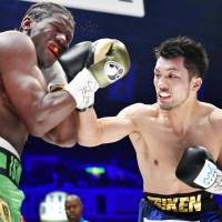 Ryota Murata lands a punch on Hassan N'Dam during their WBA middleweight world title fight on Sunday at Ryogoku Kokugikan. | KYODO