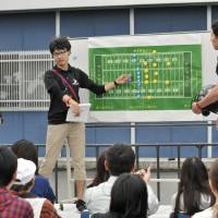 Ryuji Kashiwabara (left), and Fujitsu linebacker Shoki Cho, give a lecture about American football to fans of otaku culture before the Frontiers' game against Tokyo Gas on Sept. 23 at Fujitsu Stadium Kawasaki. | HIROSHI IKEZAWA