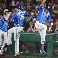 The BayStars' Jose Lopez (right) celebrates with teammates after hitting a two-run home run in the fourth inning on Tuesday in Game 3 of the Central League Climax Series Final Stage at Koshien Stadium. Yokohama defeated the Hanshin Tigers 6-1. | KYODO