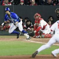 Yokohama's Masayuki Kuwahara hits a game-tying double in the fifth inning of the BayStars' 4-3 win over the Carp in Game 4 of the Central League Climax Series Final Stage on Monday in Hiroshima. | KYODO
