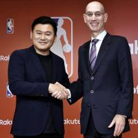 Rakuten CEO Hiroshi Mikitani and NBA commissioner Adam Silver shake hands after announcing a media partnership at a news conference in Tokyo on Tuesday. | YOSHIAKI MIURA