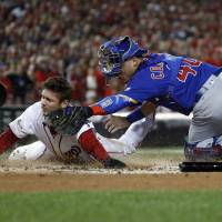 Chicago's Willson Contreras tags out Washington's Trea Turner at home plate in the first inning of Game 5 of the National League Division Series on Thursday night. | AP