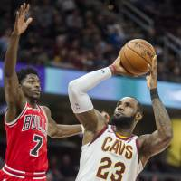 LeBron James (right) looks to shoot as Chicago's Justin Holiday defends during the Cavaliers' preseason game against the Bulls on Tuesday. | AP