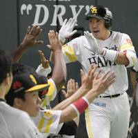 The Hawks' Seiichi Uchikawa is congratulated by teammates after hitting a solo home run in the sixth inning. Uchikawa homered for the fourth straight game in the series. | KYODO