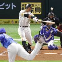 The Hawks' Yuya Hasegawa belts a two-run home run in the second inning against the BayStars on Saturday night in Game 1 of the Japan Series. Fukuoka SoftBank routed Yokohama 10-1 at Yafuoku Dome. | KYODO
