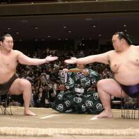 Yokozuna Hakuho (left) and Kisenosato perform the rare sandan-gamae ritual at the Beyond 2020 Basho on Wednesday at Ryogoku Kokugikan. | KYODO