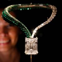 A staff member poses behind 'The Art of de Grisogono,' a necklace suspending a 163.41-carat, D color, flawless, IIA type diamond, during a preview of Christie's auction sale in Geneva Nov. 8. | REUTERS