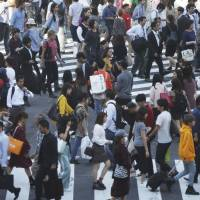 People cross streets at Tokyo's shopping and entertainment district of Shibuya in Tokyo in September. Japan reported its economy expanded at a 1.4 percent annualized rate in July-September, slowing from the previous quarter. | AP