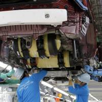 Toyota Motor Corp. workers install hydrogen storage tanks into a Mirai fuel cell vehicle, at the automaker's Motomachi plant in Toyota, Aichi Prefecture, on Oct. 30. | AP