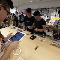 Customers try out Apple Inc. iPad products at a SoftBank Group Corp. store in Tokyo. Apple Inc. is said to be working on a redesigned, high-end iPad for as early as 2018. | BLOOMBERG
