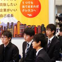 University students listen to a company presentation at Rikunabi Live, a job fair hosted by Recruit Career Co. at the Makuhari Messe convention center in Chiba, in March. | BLOOMBERG
