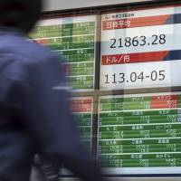 A man walks past an electronic stock board showing the Nikkei 225 index at a securities firm in Tokyo on Oct. 31. | AP