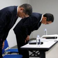 Nissan Motor Co. Chief Executive Hiroto Saikawa, flanked by Chief Competitive Officer Yasuhiro Yamauchi, bows at the start of a news conference at Nissan headquarters in Yokohama on Friday. | REUTERS