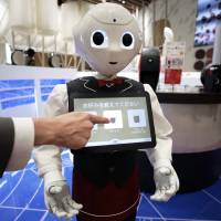 An attendee orders a cup of coffee via the touch screen on a Pepper robot during a media preview of Nestle SA's human-less cafe in Tokyo's Harajuku district Thursday. | BLOOMBERG