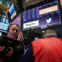 Traders work at the post where Snap and Twitter are traded on the floor of the New York Stock Exchange (NYSE) in New York Thursday. | REUTERS