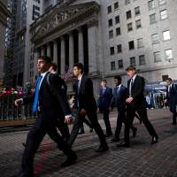 People walk along Wall Street in front of the New York Stock Exchange. | BLOOMBERG