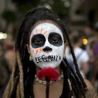A woman with the word 'Legalize' painted across her mouth marches against a recent congressional committee vote to make abortion illegal without exception nationwide, in Rio de Janeiro Nov. 13. Abortion is currently allowed in cases of rape, a pregnancy that threatens a woman's life or a fetus with anencephaly, but the committee adopted a measure that would remove those exceptions. | AP
