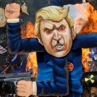 Protesters burn an effigy of U.S. President Donald Trump, who was attending the ASEAN summit in Manila on Monday. | REUTERS