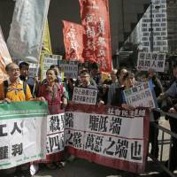 Protesters in Hong Kong hold banners during a demonstration Wednesday against evictions of the poor in Beijing. Authorities in Beijing launched sweeping evictions of workers who have migrated from elsewhere in the country, triggering a public outcry over the treatment of people the city depends on to build skyscrapers, care for children and take on other lowly paid work. The banners held by the protesters read: 'Grassroots workers residency rights, evictions of workers, end of all evil.' | AP