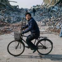 A man cycles past buildings that were destroyed by the municipality on the outskirts of Beijing Monday. The labor of hundreds of millions of migrants who moved from China's countryside to its cities has fueled the economic boom in recent decades, though legally they are not allowed access to social services outside their hometowns. But authorities in overcrowded Beijing have been getting rid of many of them for the past year as they seek to cap its population at 23 million by 2020 and demolish 40 million sq. metres of illegal structures. | AFP-JIJI