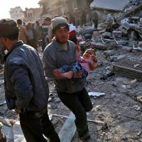 A Syrian man carries a child following a reported airstrike on the rebel-held town of Atareb in Syria's northern Aleppo province on Monday. | AFP-JIJI