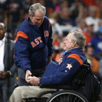 Former President George Bush hands the ball to former President George W. Bush for the ceremonial first pitch in Game Five of the World Series between the Los Angeles Dodgers and the Houston Astros at Minute Maid Park in Houston on Oct. 29. | USA TODAY / VIA REUTERS
