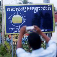 A man uses a smartphone to take photo of a sign for the opposition Cambodia National Rescue Party along a street in Cambodia's Battambang Province last month. | REUTERS