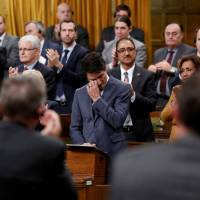 Canadian Prime Minister Justin Trudeau wipes away tears while delivering an apology to members of the LGBT community who were discriminated against by federal legislation and policies, in the House of Commons on Parliament Hill in Ottawa Tuesday. | REUTERS