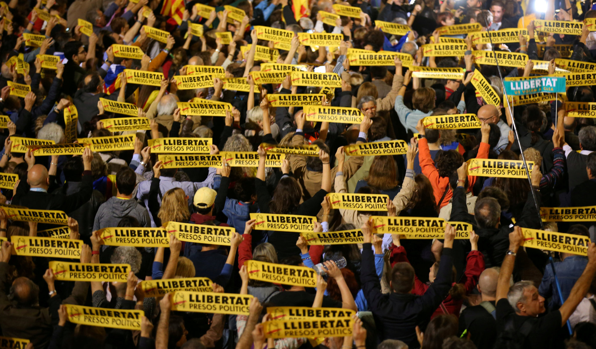 People hold banners reading, 'Free political prisoners' outside City Hall in Barcelona, Spain, on Friday during a gathering in support of the members of the dismissed Catalan Cabinet whom a Spanish judge had ordered to be remanded in custody pending an investigation into Catalonia's independence push. | REUTERS
