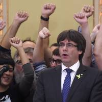 Then-Catalan regional President Carles Puigdemont (center) sings the Catalan anthem after a parliamentary session in Barcelona, Spain, on Oct. 27. | AFP-JIJI