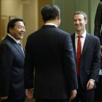 Chinese President Xi Jinping (center) talks with Facebook Chief Executive Mark Zuckerberg as Lu Wei, China's internet czar, looks on during a gathering of CEOs and other executives at Microsoft's main campus in Redmond, Washington, in September 2015. | AP