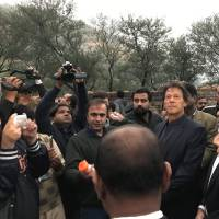 Imran Khan, chairman of the Pakistan Tehreek-e-Insaf political party, along with the members of the media, looks on during a ceremony at an archaeological site near Haripur on Wednesday. | REUTERS