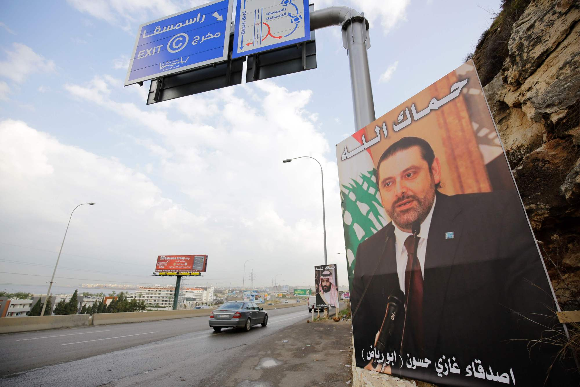 A poster of Lebanese Prime Minister Saad Hariri, who resigned last week in a televised speech, hangs on the side of a road with a phrase reading in Arabic, ' God protect you' in the northern Lebanese port city of Tripoli on Thursday. Hariri announced his resignation last weekend from Riyadh in a televised speech that sparked concerns of a political crisis in Lebanon as tensions between Saudi Arabia and Iran escalated. | AFP-JIJI