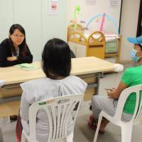 Pregnant domestic workers speak with social worker Jessica Chow at PathFinders in Tai Kok Tsui, Hong Kong, on Oct. 30. | THOMSON REUTERS FOUNDATION