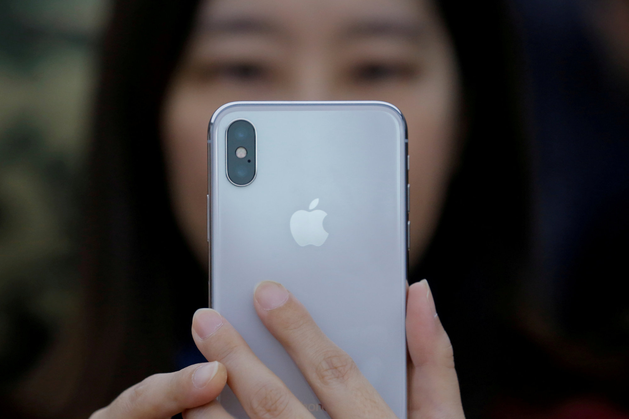 An attendee uses a new iPhone X during a presentation for the media in Beijing on Oct. 31. | REUTERS