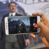 A visitor to the De Mata Museum in Yogyakarta, Indonesia, takes a photo of a wax figure of Adolf Hitler against a backdrop of the gate to the Auschwitz-Birkenau death camp on Wednesday. | AP