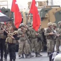 Iraqi and Turkish soldiers wave flags at the Habur Border Gate between Turkey and Iraq in this still image taken from video Tuesday. | IHA/ VIA REUTERS