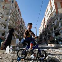 A boy rides a bicycle through the rubble of damaged buildings in the town of Sarpol-e Zahab in Iran's western Kermanshah province, near the border with Iraq, on Tuesday, following a magnitude 7.3 earthquake that left hundreds dead and thousands homeless two days earlier. | AFP-JIJI