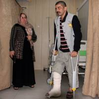 An earthquake victim is helped at Sulaimaniyah Hospital on Sunday in Sulaymaniyah, Iraq. | AFP-JIJI