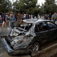 People look on at a damaged vehicle after a suicide bomb attack in Kabul Thursday. | REUTERS