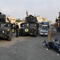 Iraqi security forces inspect the scene of a twin suicide attack at a shopping area in Iraq's disputed Kirkuk city on Sunday. The attackers struck near a former police station used by Saraya al-Salam, a Shiite paramilitary force led by powerful Shiite cleric Moqtada al-Sadr, the official said on condition of anonymity. | AFP-JIJI