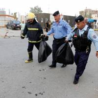 Policemen and a firefighter carry bags containing remains of the suicide bomber, in Kirkuk, Iraq, Sunday. | REUTERS