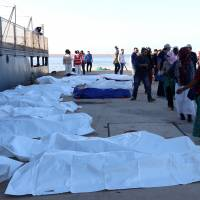 Bags containing bodies of migrants who died when a boat sank off Libya's western coast, are seen in Tripoli Saturday. | REUTERS