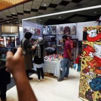 Libyan gather at a stall during the Libya Comic Convention in Tripoli on Thursday. | AFP-JIJI