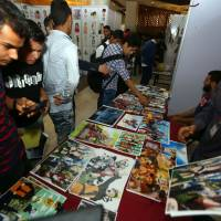Libyans gather at a stall selling posters at the Libya Comic Convention in Tripoli on Thursday before it was shut down by the Deterrence Force. | AFP-JIJI