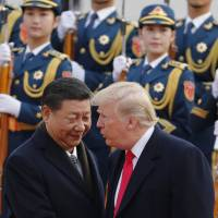 U.S. President Donald Trump chats with Chinese leader Xi Jinping during a welcome ceremony at the Great Hall of the People in Beijing on Nov. 9. | AP